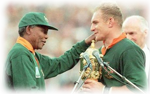 President Nelson Mandela hands the William Webb Ellis Cup over to Captian Francios Pienaar after South Africa won the 1995 Rugby World Cup